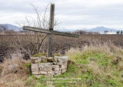 Ein betont schlichtes Holzkreuz befindet sich wenige Meter abseits der Bahntrasse an einem Feldweg. © WILDFISCH