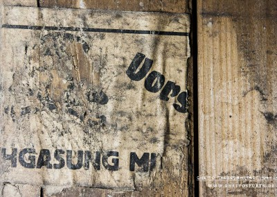 """Dass Giftgas für die Durchgasung der Kellerräume benutzt wurde, belegt dieses Stück Papier an einer ehemaligen Zellentür. Ein Schädel mit gekreuzten Knochen (Totenkopfsymbol), das traditionelle Piktogramm für Gift, und eine Warnung in deutscher Sprache weisen auf die Gefahr hin: """"Vorsicht DUCHGASUNG MIT GIFTGAS"""".Text: © Uta Fischer,  All rights reserved"""