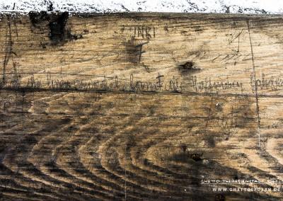 """""""Bůh s námi"""" (deutsch """"Gott mit uns""""). Ins Auge fallen sofort die mittig angeordnete  Inschrift """"INRI"""" und ein Doppelkreuz, auch Patriarchenkreuz genannt. Darunter ist in Sütterlin geschrieben: """"Ihr die ihr hier eintretet, lasst die Hoffnung fahren,"""" und """"Dante"""". Es handelt sich um ein Zitat von Dante Alighieri aus dem Stück """"Die göttliche Komödie"""" (La Divina Commedia). Alighieri (1265 – 1321) war ein italienischer Dichter und Philosoph, der als bedeutendster Dichter des europäischen Mittelalters gilt. *  (Dies ist eine von wenigen Inschriften, die Häftlinge in deutscher Sprache hinterließen.)  *Dante Alighieri, Die göttliche Komödie (La Divina Commedia); Erstdruck Foligno 1472. Übers. v. Karl Witte, Berlin, Askanischer Verlag 1916 Text: © Uta Fischer,  All rights reserved"""