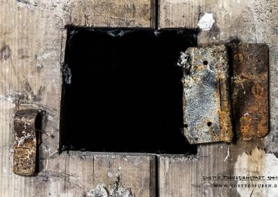 Überwachungsöffnung in einer Zellentür. Von der Klappe ist nur noch das Scharnier vorhanden. Text: © Uta Fischer,  All rights reserved