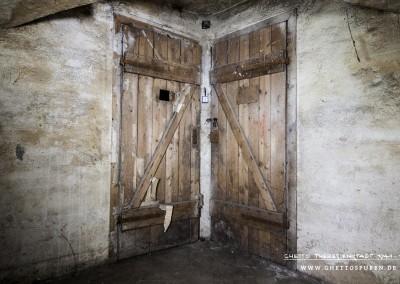 """Türen der Zellen Nr. 6 und 7 einschließlich der Schlösser sind bis heute erhalten. An der Tür zur Zelle Nr. 6 hängen noch Fetzen von Papier, die sehr wahrscheinlich auch der Zeit des Ghettos zuzuordnen sind.  Solches Papier verwendete man unter anderem, um Ritzen vor Zugluft abzudichten. Wesentlich wahrscheinlicher ist jedoch, dass die Türen im Rahmen einer Desinfektion abgedichtet wurden. Wanzen und Läuse wurden zu dieser Zeit mittels Giftgas bekämpft. Sowohl die SS als auch die jüdische Selbtstverwaltung verwendeten hierfür das in den 20er Jahren entwickelte hochgiftige Insektizid Zyklon B.  Käthe Starke arbeitete in der Abteilung """"Entwesung"""" der Selbtstverwaltung und beschreibt sehr detailliert die Prozedur: """"Der Kampf gegen das Ungeziefer wurde mit Giftgas geführt. Spezialtrupps dichteten die Räume an Türen und Fenstern mit Papierstreifen ab, wenn ihre Insassen sie mitsamt ihrer Habe verlassen hatten. Mit Gasmasken geschützt, öffneten die gleichen Kommandos Türen und Fenster nach einer angemessenen Zeit wieder. Aber danach hatten wir ohne Atemschutz in einer Luft zu arbeiten, die heftig in die Lungen stach, und der Leim, mit der das Papier verklebt wurde, war beste Qualität und mit kalten Wasser kaum zu lösen."""" *  Der Rest eines Zettel mit einer Warnung vor dem Einsatz von Giftgas (in deutscher Sprache) ist ebenfalls erhalten geblieben und belegt, dass im Keller Giftgas eingesetzt wurde. Der von Käthe Starke erwähnten """"besten Qualität"""" des Leims ist anscheinend zu verdanken, dass diese auf den ersten Blick unscheinbaren Spuren bis heute erhalten geblieben sind.   *Käthe Starke: Der Führer schenkt den Juden eine Stadt, Berlin 1975, S. 37, 54    Text: © Uta Fischer,  All rights reserved"""