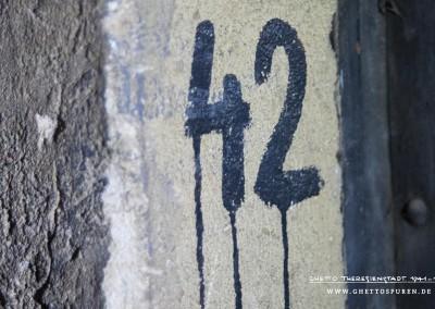 """Die Wandbeschriftung """"42"""" befindet sich neben einer Tür auf dem großen Dachbodenraum. Die Systematik der Raumbezeichnungen war stets gleich: Ziffer """"4"""" steht für die Etage, die Ziffer  """"2"""" bezeichnet die konkrete Raumnummer in der  Etage. Infolge von veränderten Raumaufteilungen oder Nutzungen kam es zu Änderungen der Raumbezeichnungen. Diese Bezeichnung stammt aus der Zeit, als auf dem Dachboden bereits keine Häftlinge mehr wohnten. Text: Uta Fischer © 2014, All rights reserved. Foto: © WILDFISCH"""