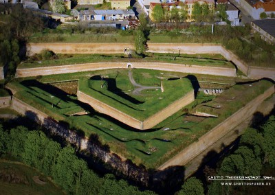 Birds-eye-view: The aerial photograph shows the northwestern section with Ravelin XVIII, a fortress defense wall system. This part of the fortress has been recently developed for tourism and also serves as a pedestrian zone for Terezin's residents. Visible in the photo where grasses stand over three feet tall, there used to be kitchen gardens where prisoners were forced to grow fruits and vegetables for the SS.