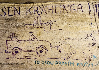 """Ein Cartoon zeigt im Hintergrund die Prager Burg und eine untergehende Sonne. Im Vordergrund fährt ein Auto gezogen von zwei Kühen. Auf dem Rücksitz sitzt eine Frau, einen Fahrer mit Mütze gibt es auch. Das Bild ist beschriftet mit """"SEN KRÝCHLINGA – TO JSOU PROSÍM KRÁVY"""" (deutsch: """"Der Traum des Kriechlings. Das sind Kühe bitte"""". Text: Uta Fischer © 2014, All rights reserved"""