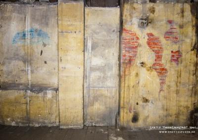 Eine Bretterwand, die zum Bestand des Dachbodens gehörte, wurde verkleidet mit Heraklithplatten, einem damals häufig verwendeten Dämmstoff. Diese wurden verputzt und später von Häftlingen individuell auf diese Weise gestaltet. Text: Uta Fischer © 2014, All rights reserved