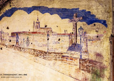Ein Motiv, das jeder Tscheche kennt: Die Karlsbrücke in Prag, die die Altstadt mit der Kleinseite verbindet, war für viele Prager Juden, die fern ihrer Heimatstadt in Theresienstadt festgehalten wurden, ein Sehnsuchtsmotiv. Karlsbrücke und Prager Burg (im Hintergrund) sind die Wahrzeichen der böhmischen Hauptstadt; auch das dürfte ein Grund für das Motiv des Malers gewesen sein. Theresienstadt liegt nur 60 Kilometer von Prag entfernt. Die unübersehbare Beschädigung der Wand, sie ist regelrecht durchlöchert, stammt vermutlich aus späterer Zeit.  Text: Uta Fischer © 2014, All rights reserved