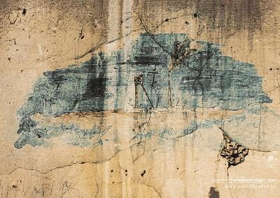 """Nur zwei Farben (Blau und Braun) benötigte der Urheber der Wandmalerei für dieses realistisch anmutende Bild. Vieles spricht dafür, dass es einen konkreten Ort zeigt. Zu erkennen ist eine Förderanlage mit Förderturm und Gebäudegruppe. Im Hintergrund ein hoher Schlot, aus dem eine große Rauchwolke aufsteigt.   Sehr wahrscheinlich ist, dass ein Häftling hier ein Bergwerk malte, in dem er zuvor in einem sogenannten Außenkommando im Arbeitseinsatz war. Die Bergbaudirektion der Prager Eisenbahngesellschaft forderte im Februar und März Arbeitskräfte aus Theresienstadt an, um diese in ihren Bergwerken in Kladno einzusetzen. Der Zeitraum war beschränkt auf Februar 1942 bis Juli 1943. Die Häftlinge arbeiteten u.a. in den Minen """"Ronna"""", """"Mayrau"""" und """"Schoeller"""", außerdem auch für die Steinkohlen AG Lány-Rakovník im Bergwerk Prago in Dubí. Text: Uta Fischer © 2014, All rights reserved"""