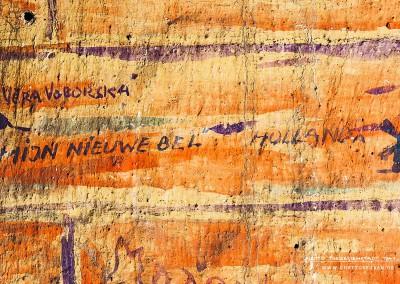 """Ein Hügel mit Kreuz, daneben der tschechische Name """"VĚRA VOBORSKÁ"""". Der Name ist in der Datenbank der Häftlinge des Ghetto Theresienstadts nicht gelistet. """"MIJN NIEUWE BEL"""" ist niederländisch und heißt auf Deutsch """"Meine neue Klingel [oder Glocke]"""", daneben sind in kleinem Abstand die Inschrift """"HOLLANDA"""" und eine winzige Windmühle zu erkennen.  Dieses Graffito ist auf den ersten Blick ein wertvoller Hinweis auf die Herkunft des Urhebers. In Theresienstadt waren etwa 6.000 Juden aus den besetzten Niederlanden interniert, darunter viele Deutschniederländer, die zuvor in die Niederlande immigriert waren. Sie kamen ab April 1943 in Theresienstadt an. Merkwürdig ist jedoch, dass beide Inschriften sich sehr ähnlich sind. Naheliegend ist, dass ein und dieselbe Person die beiden Inschriften hinterließ.  Text: Uta Fischer © 2014, All rights reserved"""