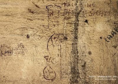 """Ein Koch hält einen Sack in der Hand: Er ist beschriftet mit """"JIŠKA"""", deutsch Mehlschwitze. Zu dem Cartoon gehörte ein Text, doch der ist  kaum noch vorhanden. Lediglich die Fragmente """"KRÝ[...]NG"""" wie Kriechling und """"ŠICHT""""(deutsch Schicht) sind noch lesbar. Die Inschrift ist ein Hinweis darauf , dass  zumindest ein  Bewohner als Koch in einem Kriechlingsheim tätig gewesen sein könnte. Köche arbeiteten  in Theresienstadt im Schichtbetrieb. Text: Uta Fischer © 2014, All rights reserved"""
